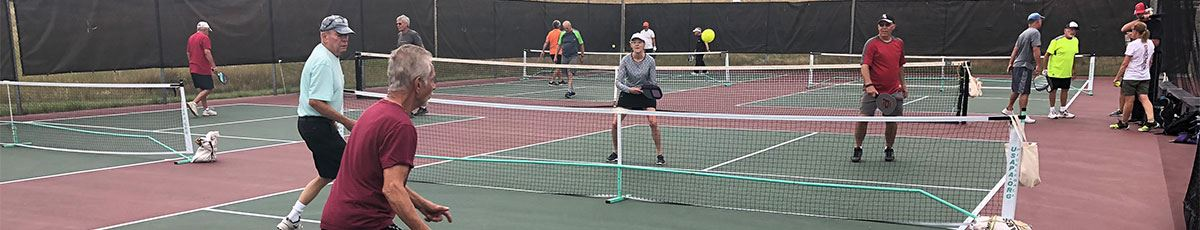 Adults playing Pickleball on outdoor court
