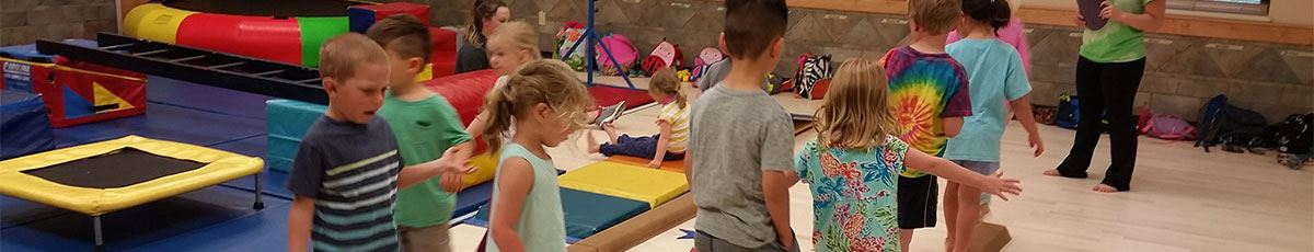 Gymnastics camp with kids on balance beam trainer
