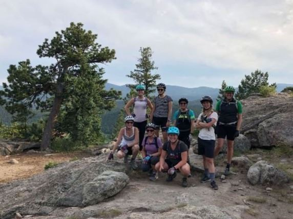 Women's mountain biking class with group photo on hilltop