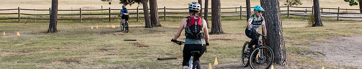Skills course for women's mountain bike class with bikers going around obstacles