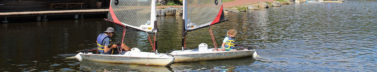 Kids sailing camp with child and instructor in separate sail boats