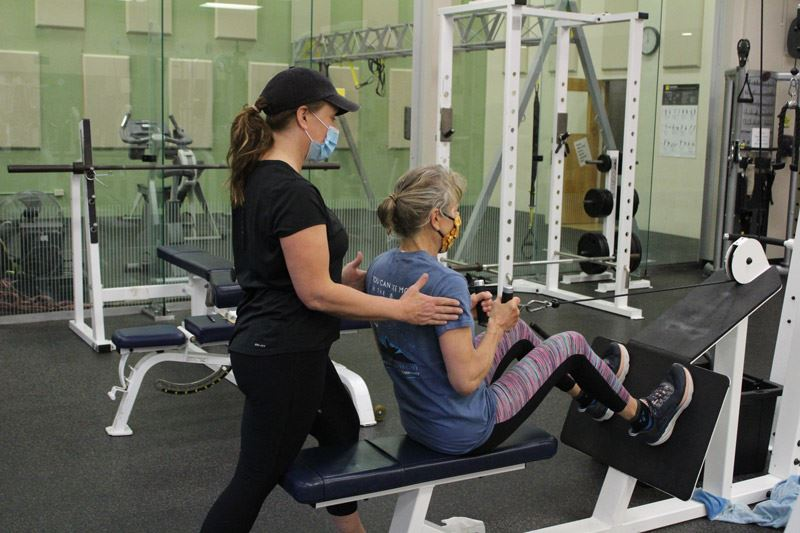 Personal training at Wulf Recreation Center with female trainer and female client on equipment