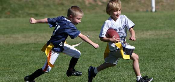 Two Young Boys Playing Flag Football