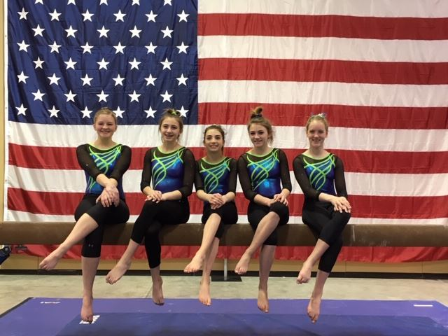 Five Uniformed Gymnasts Sitting on a Balance Beam
