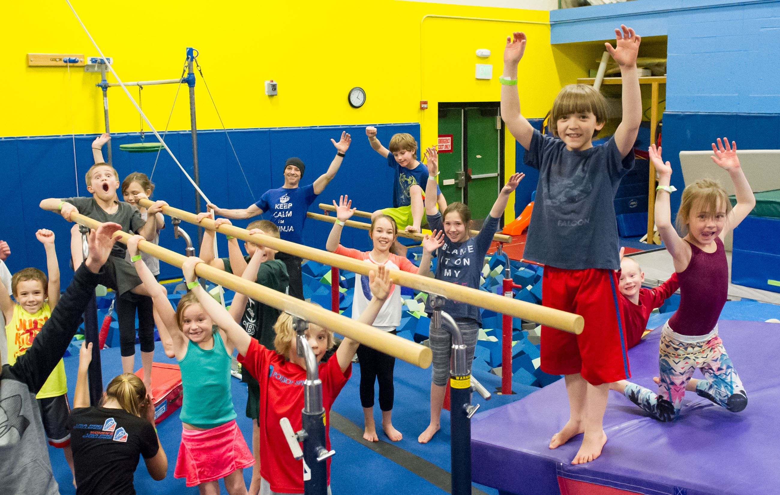 Kids Standing Around Fun Gym Equipment with Hands Raised Over Their Heads