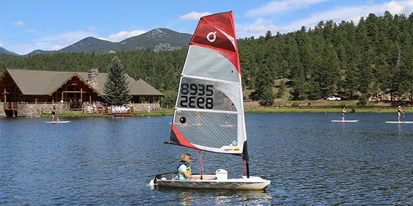 Sailing camp on Evergreen Lake with child in small sailboat